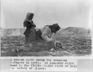 Donna armena inginocchiata accanto al corpo d'una bambina morta nei campi